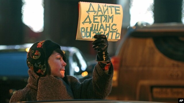 A woman opposing a bill that would ban adoptions of Russian children by Americans holds a sign reading 'Give the children a chance to live' during a picket at the entrance of the State Duma, in Moscow, Russia, December 21, 2012.