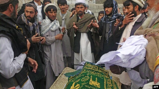 Afghan men pray during the funeral of Najia Sidiqi, the acting director of the women's affairs department in Mihtarlam, December 10, 2012.