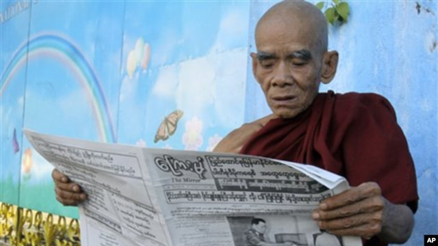 A Buddhist monk reads a newspaper outside the Jivita Dhana Free Hospital for Buddhist Monks in Rangoon, Burma, one day after the first elections in 20 years, 08 Nov. 2010.