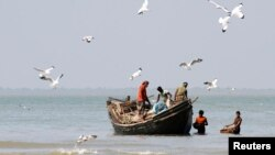 FILE - Fishermen catch fish at the shores of Bay of Bengal at Dublar Char in the Sundarbans, Bangladesh.