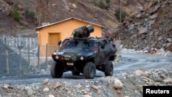 FILE - A Turkish military armored personnel carrier drives past a small patrol base in the mountains of Cukurca in southeastern Turkey, near the Iraqi border, Oct. 21, 2011.