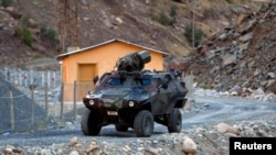 FILE - A Turkish military armored personnel carrier drives past a small patrol base high in the mountains of Cukurca near the Iraqi border in southeastern Turkey. Syria slammed Turkey on Dec. 6, 2015, for deploying hundreds of troops in neighboring Iraq.