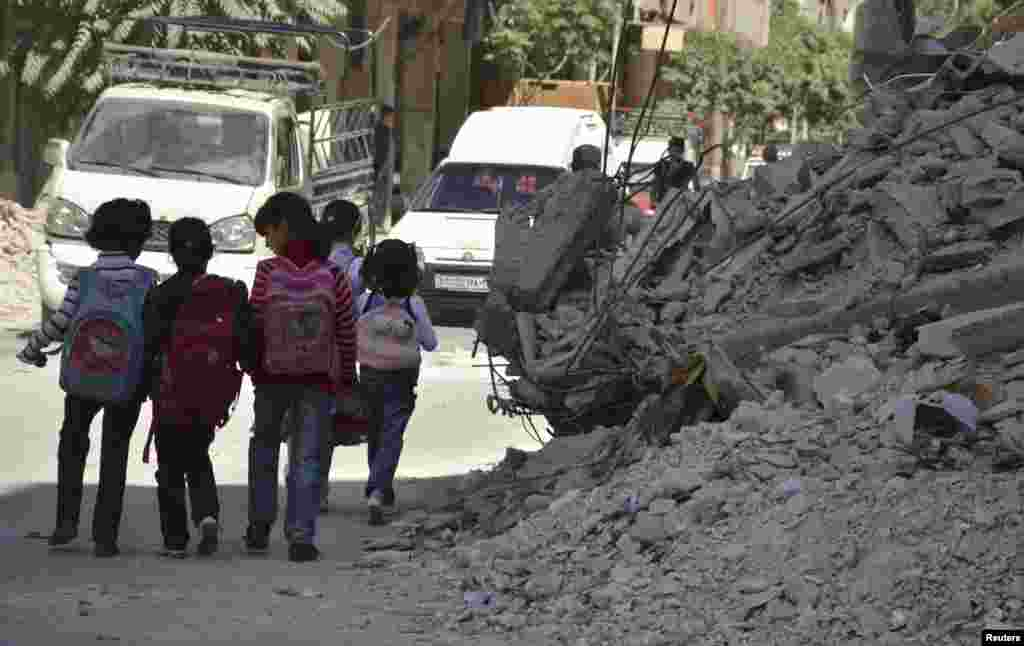 Children walk through damaged streets as they go to school in the Duma neighbourhood in Damascus, Sept. 29, 2013.
