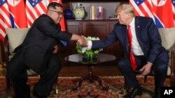 Le président des États-Unis, Donald Trump, serre la main du dirigeant nord-coréen Kim Jong Un lors de leurs premières rencontres au resort de Capella sur l'île de Sentosa, le 12 juin 2018 à Singapour.