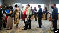 FILE - People are seen waiting in line to meet with recruiters during a job fair in Philadelphia, Pennsylvania.