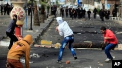 Egyptian protesters throw stones at riot police during clashes near a state security building in Port Said, March 7, 2013.