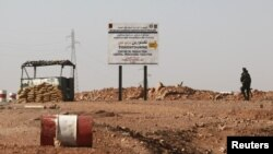 An Algerian soldier stands at a checkpoint near a road sign indicating 10 km (6 miles) to a gas installation in Tigantourine, the site where Islamist militants have been holding foreigners hostage according to the Algerian interior ministry, in Amena Janu