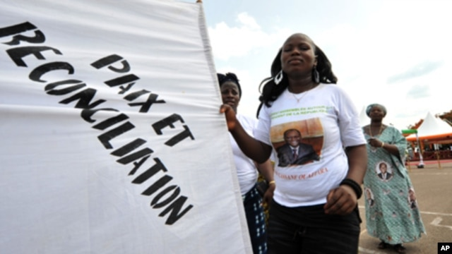 "A supporter of Ivorian President Alassane Ouattara dances as she holds a banner reading in French ""Peace and reconciliation"" during a meeting on April 22, 2012 in Guiglo."
