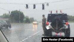 Một người lính thuộc lực lượng Vệ binh Quốc gia đứng nghiêm dưới mưa đưa tay chào một đoàn xe tang.