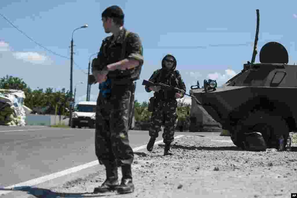 "Pro-Russian fighters from a group that calls itself ""Russian Orthodox Army"" guard at a check point in Donetsk, eastern Ukraine, June 10, 2014."