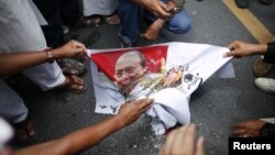 Muslims burn a picture of Burma's president Thein Sein as they protest in front of Burma's embassy in Bangkok, June 21, 2012.