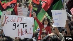 Opositores libios muestran su enojo en carteles donde reclaman la salida de Gadhafi del poder, durante una manifestación en Bengasi.