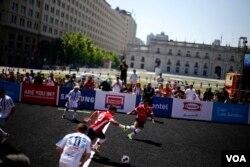Para pemain sepak bola dari tim Chile dan Argentina berebut bola dalam laga turnamen sepak bola Homeless World Cup ke-12 di Santiago, 19 Oktober 2014. (Foto: Reuters/dok)