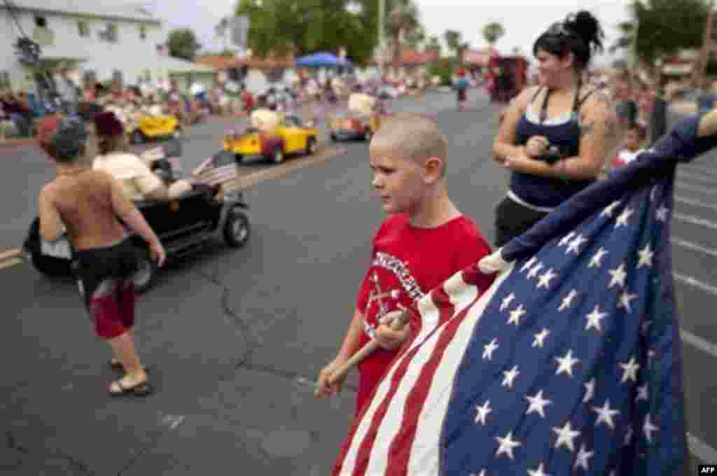 Ten-year-old Austin Kelley, right, watches as floats and other entrants roll along Nevada Way in the 63rd Annual Boulder City Damboree Parade, Monday, July 4, 2011, in Boulder City, Nev. (AP Photo/Julie Jacobson)