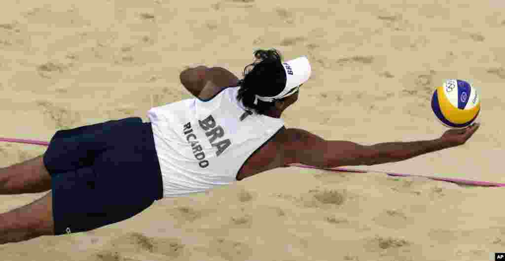 Ricardo Santos, de Brasil, salva la pelota durante un partido de vóleibol playa contra Gran Bretaña.