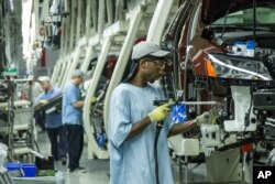 Factory work is often scheduled in shifts. In this June 2013 photo, workers assemble Volkswagen cars at the German automaker's factory in the U.S. state of Tennessee. (FILE PHOTO)