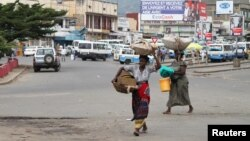 Des vendeurs portent les leurs produits, dans les rues de Bujumbura, le 3 février 2016.
