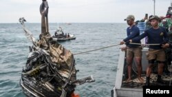 Anggota TNI AL menarik serpihan puing saat mencari sisa-sisa pesawat Sriwijaya Air penerbangan SJ 182 yang jatuh ke laut lepas pantai Jakarta, 11 Januari 2021. (Foto: Antara/M Risyal Hidayat via Reuters)