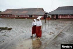 FILE - Students walk in the yard of the Pantai Bahagia Elementary School, before tide comes in, in Bekasi, West Java province, Indonesia, Feb. 1, 2018.