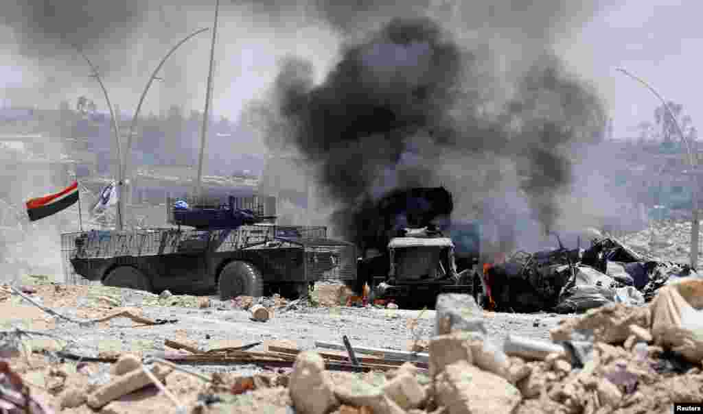 An Iraqi military armored fighting vehicle drives past a burning military truck after it was hit by the Islamic State militants during fighting in western Mosul.
