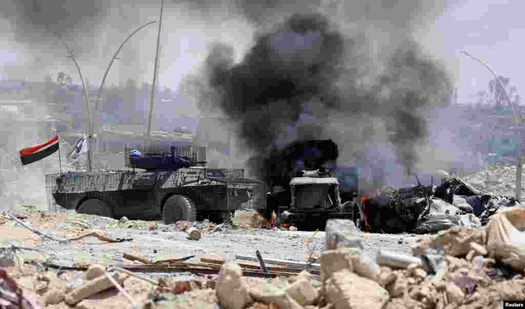 Sebuah truk militer pasukan Irak terbakar setelah terkena tembakan militan ISIS dalam pertempuran di Mosul barat.