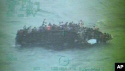 This image taken from video made available by the U.S. Coast Guard shows a group of Haitian migrants sitting on the hull of a capsized sailboat. Nov. 26, 2013, (AP Photo/U.S. Coast Guard)