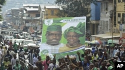 Supporters of the opposition Sierra Leone People's Party (SLPP) march through central Freetown with a placard of presidential candidate Julius Maada Bio and his running mate, Dr. Kadi Sesay, in Freetown, Sierra Leone, October 19, 2012.
