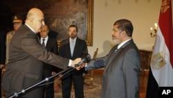 Cumhurbaşkanı Mursi (sağda), yardımcısı Mekki'nin elini sıkarken