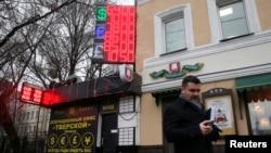 一名路人12月16日行經莫斯科一建築前﹐背後電子報表顯示盧布再創新低。