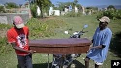 两名海地男子10月24日抬着霍乱死难者的棺木