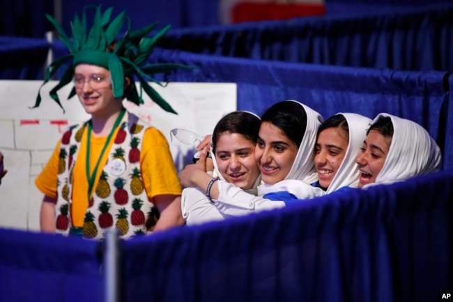 Team Afghanistan — from second from left, Kawsar Rashan, Lida Azizi, Somayeh Faruqi and Rodaba Noori — next to a member of Team Australia, at left, hug before their final round of competition at the FIRST Global Robotics Challenge, July 18, 2017, in Washington.