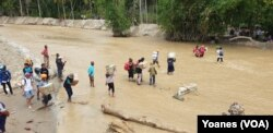 Para relawan kemanusiaan menyeberangi sungai yang mulai surut untuk mengantarkan logistik bantuan bahan makanan bagi warga terdampak banjir bandang di dusun 3, Desa Bangga, Dolo Selatan, Kabupaten Sigi, Sulawesi Tengah, 1 Mei 2019. (Foto: VOA/Yoanes)