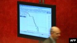 Seorang pialang Rusia melintas di depan sebuah monitor di bursa saham MICEX di Moskow (foto: dok).