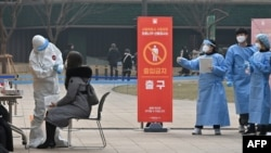 A medical staff member (L) wearing protective gear takes a swab from a visitor to test for the COVID-19 coronavirus at a temporary testing station outside the City Hall in Seoul on December 23, 2020, as South Korea banned gatherings of more than four peop
