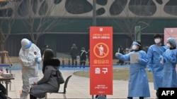 Seorang anggota staf medis (kiri) yang mengenakan alat pelindung mengambil sampel dari seorang pengunjung untuk menguji virus corona Covid-19 di stasiun pengujian sementara di luar Balai Kota di Seoul pada 23 Desember 2020. (Foto: AFP)