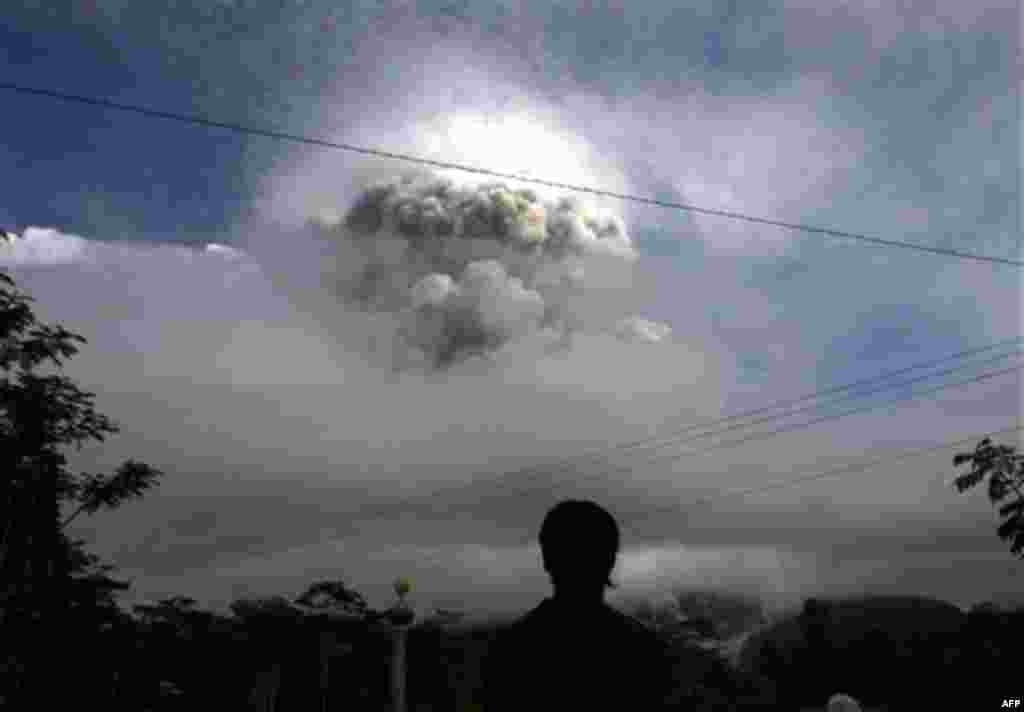 An Indonesian man watches as Mount Merapi erupts in Kepuharjo, Yogyakarta, Indonesia, Wednesday, Nov. 3, 2010. Indonesia's most dangerous volcano is once again sending searing gas clouds and burning rocks down its scorched flanks. (AP Photo/Gembong Nusant