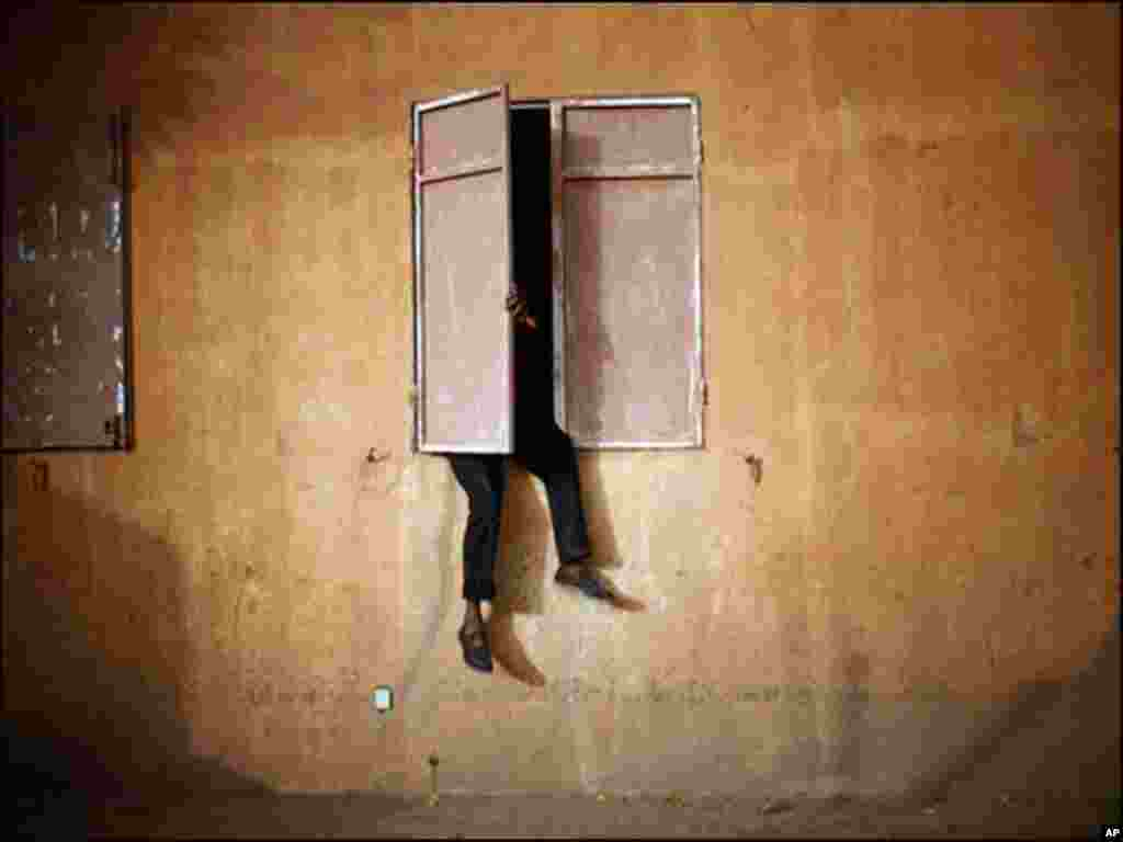 مالی میں ایک شخص کھڑکی میں بیٹھ کر فٹ بال میچ دیکھ رہا ہے