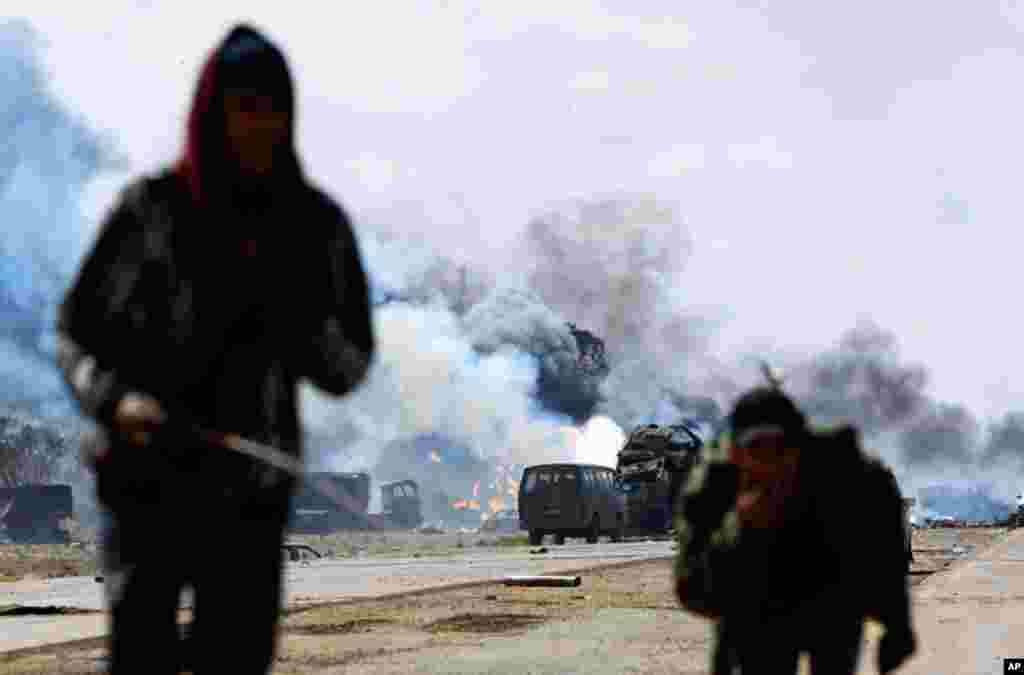 Rebel fighters run for cover on a road between Benghazi And Ajdabiya, after an air strike on March 20, 2011, by coalition leaders on forces loyal to Muammar Gadhafi. (Reuters/Goran Tomasevic)