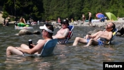Beachgoers sit in the water at Alouette Lake to cool off during the scorching weather of a heatwave in Maple Ridge, British Columbia, Canada June 28, 2021. (REUTERS/Jennifer Gauthier)