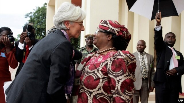 FILE - International Monetary Fund Managing Director Christine Lagarde is greeted by Malawi's President, Joyce Banda, on arrival at Kamuzu Palace in Lilongwe on her three-day official visit to Malawi, Jan. 4, 2013.