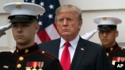 President Donald Trump stands behind and in front of members of a Marine honor guard as he greets Canadian Prime Minister Justin Trudeau and Sophie Gregoire Trudeau as they arrive at the White House in Washington, Oct. 11, 2017.