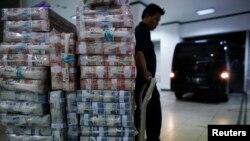 Seorang petugas menunggu untuk mengangkut uang rupiah ke kendaraan di kantor pusat Bank Mandiri, Jakarta (18/11). (Reuters/Darren Whiteside)