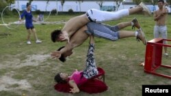 A woman (bottom) balances two men with her feet as students practice at an acrobatic school in Sanwang village, Anhui province, China, July 30, 2015. With a population of 1.37 billion, China has more men than women. The current ratio is at about 105:100.