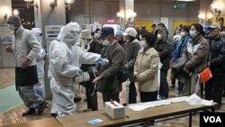 Warga Jepang yang dievakuasi diperiksa di pusat pemeriksaan di kota Koriyama berkaitan dengan radiasi yang mengancam setelah pusat pembangkit listrik tenaga nuklir rusak akibat gempa dan Tsunami.