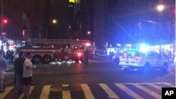 Polisi dan petugas pemadam kebakaran berada di lokasi ledakan di kawasan Chelsea, Manhattan, New York Sabtu malam (17/9).