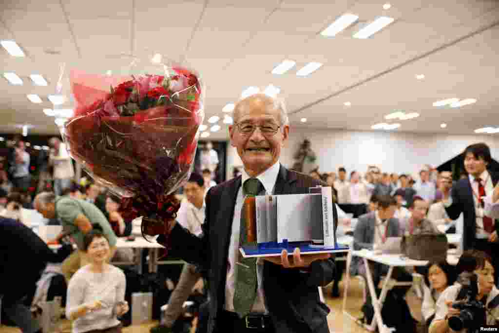 Asahi Kasei honorary fellow Akira Yoshino, 2019 Nobel Prize in Chemistry winner, holds a mock of lithium-ion battery and a flower bouquet during a news conference in Tokyo, Japan.