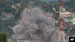 Puing-puing beterbangan saat jet tempur Angkatan Udara Filipina menggempur lokasi yang dicurigai sebagai markas militan Muslim dalam pertempuran di kota Marawi, Filipina selatan, 9 Juni 2017. (AP Photo/Aaron Favila)