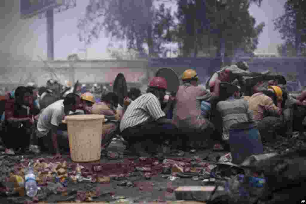 Supporters of ousted President Morsi take cover from Egyptian security forces fire during clashes in Cairo's Nasr City.