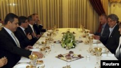 Turkey's Foreign Minister Ahmet Davutoglu (2nd L) and defected Syrian General Manaf Tlas (2nd R) meet around an Iftar dinner table as they are flanked by Turkey's intelligence agency undersecretary Hakan Fidan (L) and other officials, in Ankara, Turkey, J
