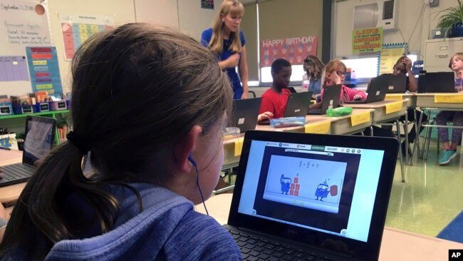 In this Sept. 20, 2018 photo, fifth grade student Ashlynn De Filippis, left, works math problems on the DreamBox system as teacher Heather Dalton, center rear, works with other students in class at Charles Barnum Elementary School in Groton, Conn. (AP Photo)